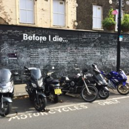 "A chalkboard on a sidewalk in London with the prompt, ""Before I die"""